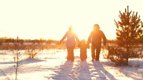 Happy family with a child walking at sunset in winter stock footage