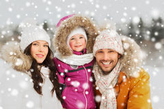 Happy family with child in winter clothes outdoors. Parenthood, fashion, season and people concept - happy family with child in winter clothes outdoors Stock Photo