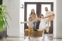Happy family with children arrived at their new house. Happy married couple and little children arrive at new modern house. Husband and wife with cardboard boxes royalty free stock photos