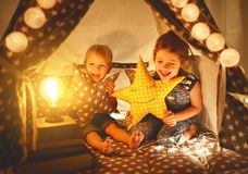 Happy family children brother and sister play, laugh and hug i. Happy family loving children brother and sister play, laugh and hug in dark tent in playroom at royalty free stock images