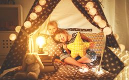 Happy family children brother and sister play, laugh and hug   i. Happy family loving children brother and sister play, laugh and hug   in dark tent in playroom Stock Photos