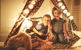 Happy family children brother and sister play, laugh and hug   i. Happy family loving children brother and sister play, laugh and hug   in dark tent in playroom Royalty Free Stock Photos