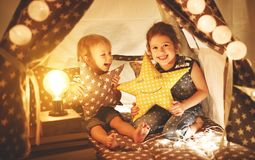Happy family children brother and sister play, laugh and hug   i. Happy family loving children brother and sister play, laugh and hug   in dark tent in playroom Royalty Free Stock Image