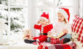 Happy family children brother and sister reading book  on winter Stock Image