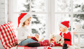 Happy family children brother and sister reading book  on winter Stock Images