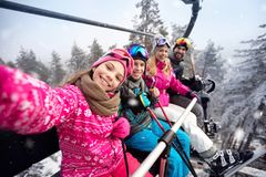 Happy family in cable car climb to ski terrain stock images