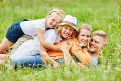 Family and kids cuddle together in the grass. Happy family and children cuddle together in the grass in the garden Royalty Free Stock Images
