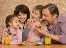 Happy family with children eating pizza Stock Photos