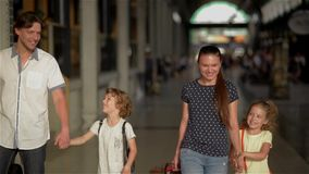 Happy family with children going on railway station, parents and kids traveling and walking on the airport. Journey stock video footage