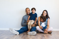 Happy family with children. Happy multiethnic family sitting on floor with children. Smiling couple sitting with two sons and looking at camera. Hispanic mother Royalty Free Stock Photography