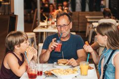 Happy family with children in outdoor restaurant stock image