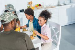 Happy family with children and parents in camouflage clothes. Enjoying breakfast royalty free stock photo