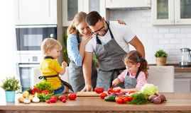 Happy family with children preparing vegetable salad Stock Photography