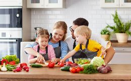 Happy family with children preparing vegetable salad Stock Image