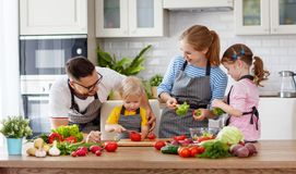 Happy family with children preparing vegetable salad Royalty Free Stock Photos