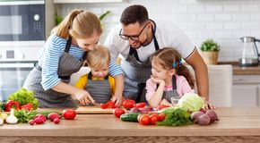 Happy family with children preparing vegetable salad Stock Photos