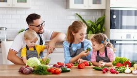 Happy family with children preparing vegetable salad Stock Photo