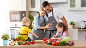 Happy family with children preparing vegetable salad Royalty Free Stock Images