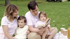 Happy family with children reading a book on a picnic outdoors. stock video footage