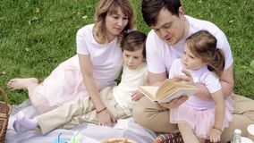 Happy family with children reading a book on a picnic outdoors.  stock footage