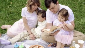 Happy family with children reading a book on a picnic outdoors. Happy family with children reading a book on a picnic outdoors stock footage