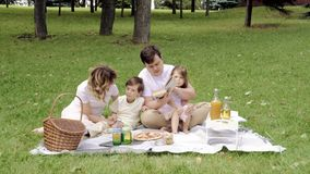 Happy family with children reading a book on a picnic outdoors. Happy family with children reading a book on a picnic outdoors stock video footage