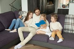 Happy family with children reading book together sitting on sofa. Happy young family with children reading book together sitting on sofa at home, smiling parents royalty free stock images