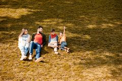 Happy family with children sitting on a grassy lawn. In autumn stock images