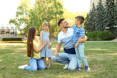 Happy family with children spending time together. In green park on sunny day royalty free stock photo