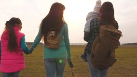 Happy family with children travel with backpacks. Teamwork of a close-knit family. Mother, little child and daughters stock video