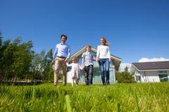Family walking on lawn near house. Happy family with children walking on lawn near their house Stock Photo