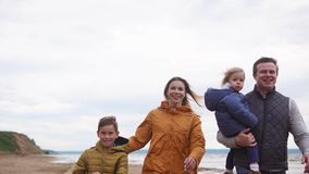 A happy family with children in warm clothes strolls by the sea on a windy day stock video footage