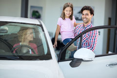 Happy family choosing car in car showroom. Young women in seat of auto Stock Photo