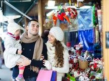 Happy family choosing Christmas decoration at Christmas market Stock Photos