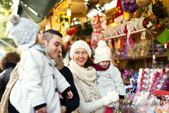 Happy family choosing Christmas decoration at Christmas market Stock Images