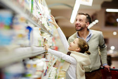 Happy Family Choosing Dairy Products in Grocery Store. Happy family grocery shopping in supermarket: smiling men with daughter choosing dairy products from Stock Image