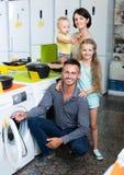 Happy family choosing washing machine Royalty Free Stock Photography