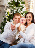 Happy family with Christmas baby near the Christmas tree Royalty Free Stock Photos