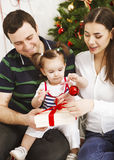 Happy family with Christmas baby near the Christmas tree Stock Images