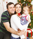 Happy family with Christmas baby near the Christmas tree Stock Photos