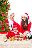 Happy family in Christmas eve at home sitting near Stock Photo