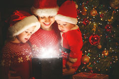Happy family on Christmas Eve. mother and children discover a ma Stock Images