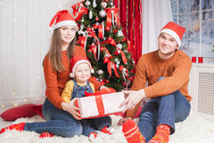Happy family at Christmas eve sitting together near decorated tree Royalty Free Stock Photo