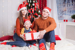 Happy family at Christmas eve sitting together near decorated tree Royalty Free Stock Photos