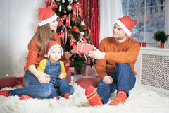 Happy family at Christmas eve sitting together near decorated tree Stock Photo