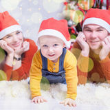 Happy family at Christmas eve sitting together near decorated tree. Happy family at Christmas eve lying together near decorated tree at living room, home. They royalty free stock photo