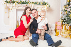 Happy family at Christmas eve sitting together near fireplace Royalty Free Stock Photo