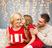 Happy family with christmas gift kissing. Holidays, family and people concept - happy girl kissing her mother with christmas gift over lights background Royalty Free Stock Photo