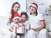 Happy family with Christmas gift sitting on a sofa in the nursery. Happy family in Christmas.the concept of family happiness. the photo has a blank space for stock images