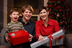 Happy family with christmas gifts. Portrait of happy family sitting at couch, holding christmas gifts, laughing Royalty Free Stock Images
